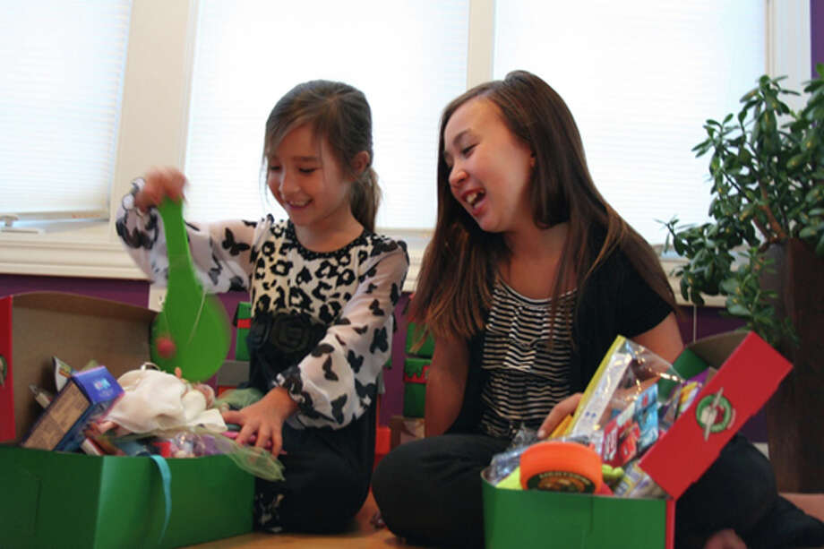 From left, sisters Sienna, 6, and Megan, 10, Mattichak pull toys out from a shoebox they will soon donate to Operation Christmas Child. The two have been collecting shoeboxes filled with Christmas toys to give to children living in other countries since Megan was 3 years old. Sienna started helping as she got older. This year for Megan's birthday she asked her friends to bring her toy-filled shoeboxes instead of a birthday present. Photo: LISA SATAYUT | For The Daily News