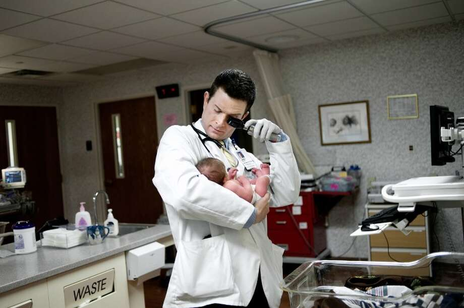 NICK KING   nking@mdn.netThird-year medical student John Evans checks out a newborn in the Maternity Unit at MidMichigan Medical Center-Midland. Evans chose to come to the MSU College of Human Health Midland Regional Campus. Evans, along with two other students, shadow physicians in family medicine, internal medicine, pediatrics, obstetrics and gynecology, surgery and psychiatry. Photo: Midland Daily News