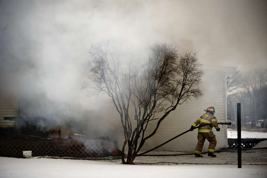 SEAN PROCTOR | sproctor@mdn.netA Lee Township Firefighter pulls a hose around the corner of a house while battling a fire on East Gordonville Road on Wednesday morning. Firefighters from Midland, Lee, Homer, Breckenridge-Wheeler and Jonesfield-Lakefield townships responded to the scene. Photo: Sean Proctor/Midland  Daily News