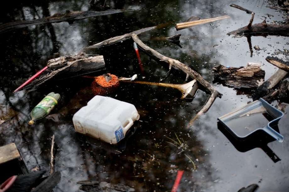 Dumped items can be seen in a puddle of water on state land in Midland County in this Daily News file photo.