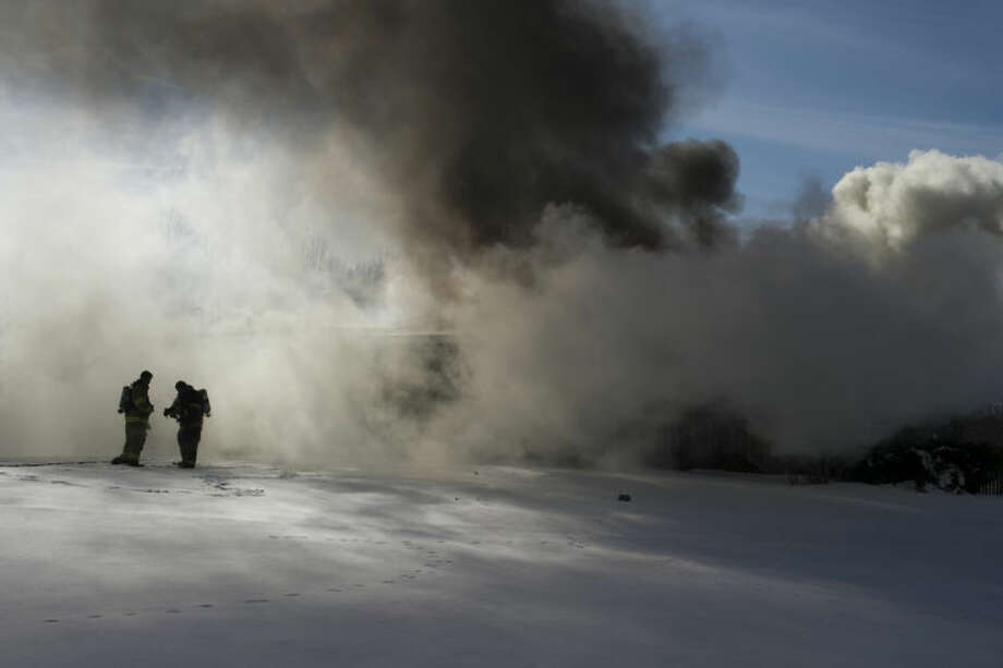 NEIL BLAKE | nblake@mdn.netFirefighters prepare to battle a blaze that swept through a home on North Swede Road on Monday. Firefighters from Mills, Hope, Larkin and Garfield townships responded to the blaze that engulfed Rodney and Kim Sweet's home. Photo: Neil Blake/Midland  Daily News