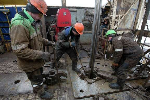 Oil workers adjust a pipe section at the turntable on an oil derrick in an oilfield in the village of Otrada, Russia. After a promising start on keeping its pledge to cut production, Russian production is now just over halfway to the reduction Moscow promised. Compliance from the 11 non-OPEC participants — estimated at just 64 percent in February — will come under scrutiny at a ministerial meeting in Kuwait City on Sunday.
