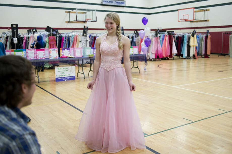 "NEIL BLAKE | nblake@mdn.net Carrie Cook of Bay City shows off her prom dress that she picked out at ""Share the Memories"" at the North Midland Family Center on Thursday. Cook is a student at Bay City Central High School. This is the fifth year for the event which repurposes prom dresses. Becca Tointon decided to start the event when she wanted to donate four dresses in her closest but couldn't find a local outlet to donate them to. This year, they had 400 new dresses along with others donated from previous years. Photo: Neil Blake/Midland  Daily News"