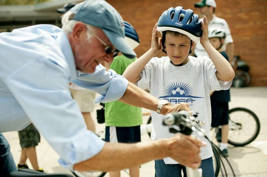 THOMAS SIMONETTI | tsimonetti@mdn.net Nathan Johnson, right, adjusts his helmet while volunteer Dave Waite readies his bike at a bike safety training at Siebert Elementary on Thrusday. Four classes of fourth and fifth graders took the training. Photo: Thomas Simonetti