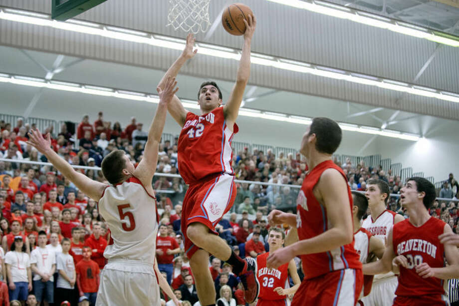 NICK KING | nking@mdn.netBeaverton's Austin Schneider, right, shoots over Laingsburg's Sam Edwards during the second period Tuesday at Delta College. Laingsburg won the boys' basketball Class C quarterfinal game 42-32. Photo: Nick King/Midland  Daily News
