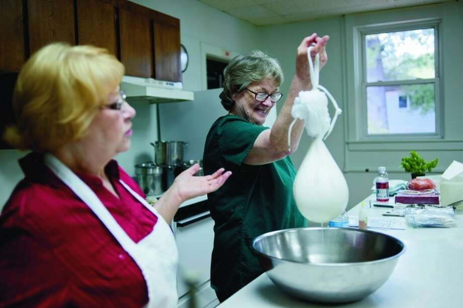 "NICK KING | nking@mdn.netFriend Toni Krause, right, drains a cloth of soft cheese as Mary Jane Toth, of Coleman, left, teaches a class on how to make cheese at the Geneva Township Hall. Toth is conducting another class on May 19. Toth has written several books about making cheese. Her newest book is called ""A Cheesemaker's Journey."" Photo: Nick King/Midland  Daily News"