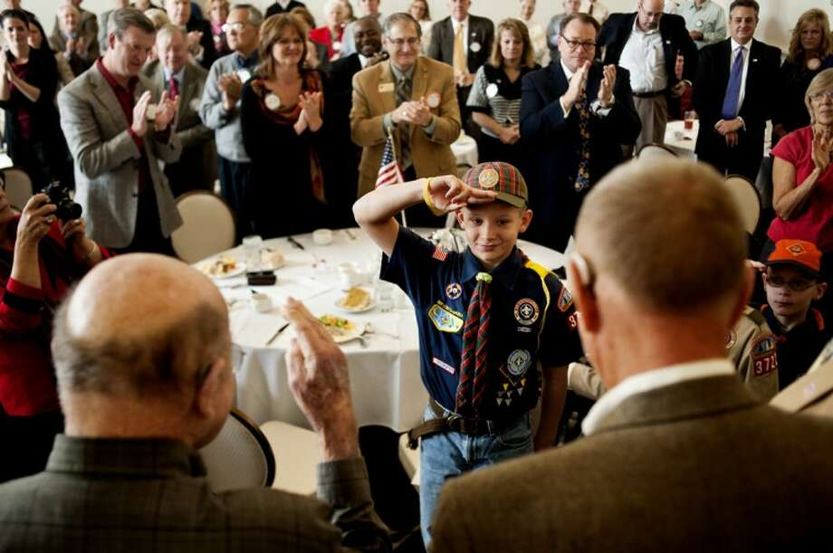 """John White, 10, a fifth year scout in Pack 3758, salutes veterans in the Midland Rotary Club, Thursday afternoon at the Midland Country Club. """"It was very cool watching all the veterans go up,"""" he said. Mike Merrill, a World War II veteran, and Chuck Coté, a Vietnam veteran, shared stories from their time in the armed forces to the audience. The Rotary Club decided to recognize the some three dozen members of the club who served during a time of war. The recognition ceremony fell on the 246th birthday of the Marine Corps, of which Coté was a member. """"This is the greatest country in the world. There is no better place to be,"""" he said during his talk. """"No matter the service, you take a solemn oath to defend this country. I would do it again."""" Photo: SEAN PROCTOR 