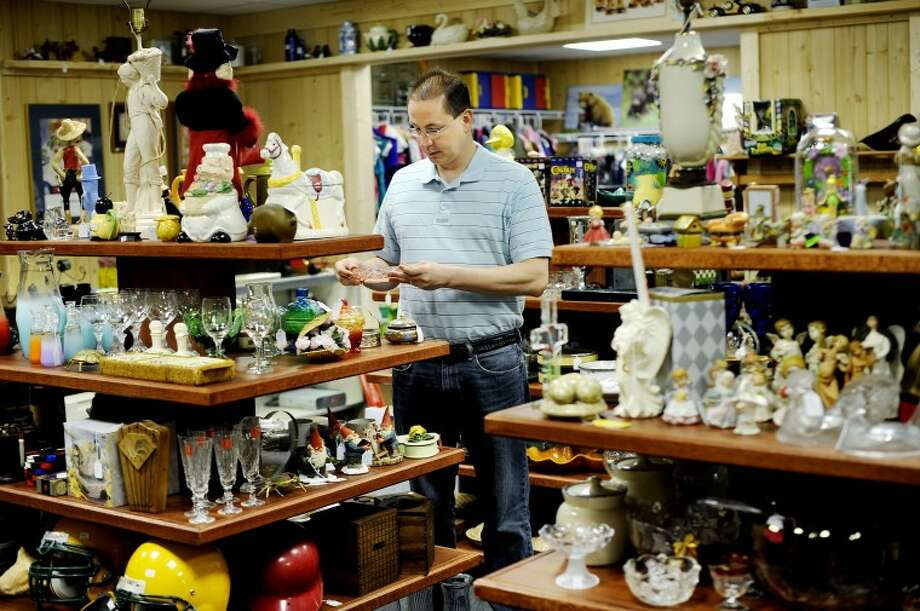 NICK KING | nking@mdn.netDean Holsworth works in the newly-added resale shop portion of Holsworth's Coins and Collectibles in Sanford. In addition to coins, gold, silver and scrap metal, Holsworth now sells various items including glassware, snow boards, clothes and collectibles. Photo: Nick King/Midland  Daily News