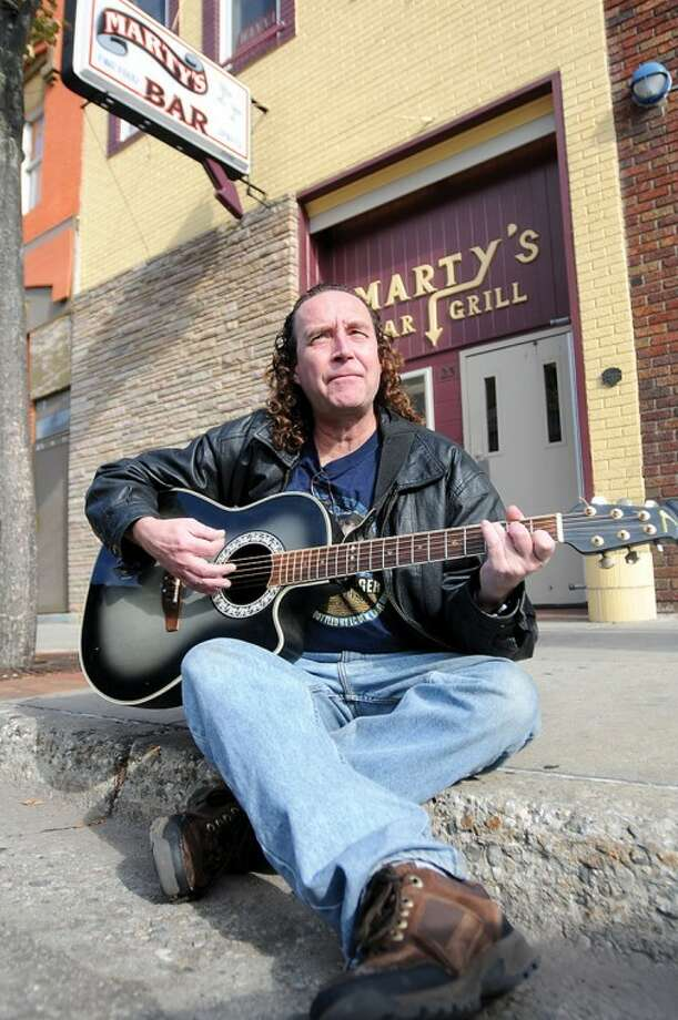 "AP Photo | The Morning Sun, Lisa Yanick-JonaitisIn a Friday, Oct. 28, photo, Bob Bacon of Mount PLeasant sings his song ""Stuck Behind Bars"" in front of Marty's Bar and Grill in Mount Pleasant, where he filmed a video for the song earlier this year. Photo: Lisa Yanick\u002dJonaitis"