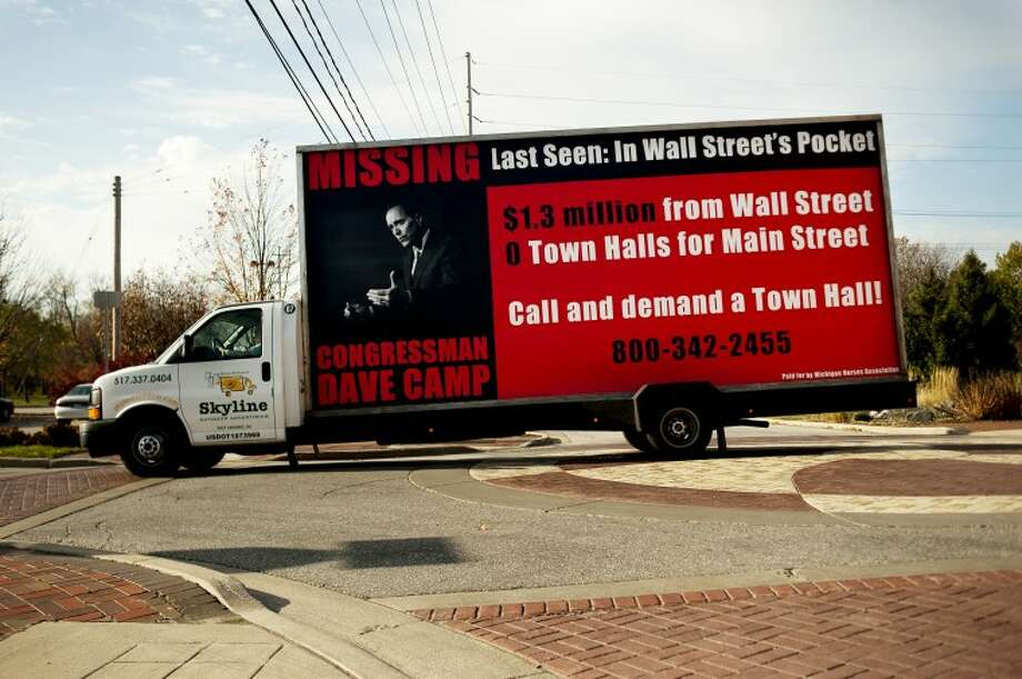 NEIL BLAKE | nblake@mdn.netA signboard truck paid for by the Michigan Nurses Association drives through downtown Midland on Thursday with a billboard demanding a town hall meeting with Congressman Dave Camp. The truck was commissioned in conjunction with radio spots urging the meetings. Ads were also run in Congressman Fred Upton's district, who is on the deficit supercommittee with Camp that is making recommendations to cut the federal budget.