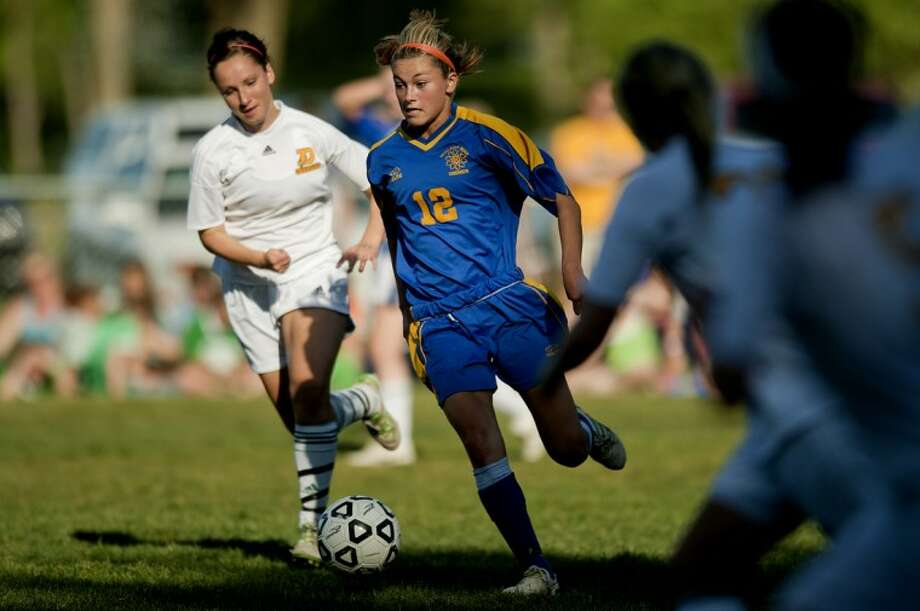 NICK KING | nking@mdn.net Midland's Nicole Meeks, right, moves past Dow's Darcy Lehman during the second half Wednesday at Dow High School. Dow won 2-0. Photo: Nick King/Midland  Daily News