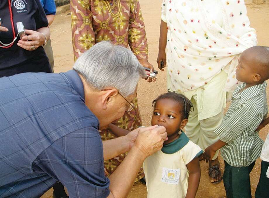 Dick Dolinski | for the Daily NewsMidlander Dick Dolinski administers oral polio vaccine to one of a set of twin girls in the streets of Kaduna. Photo: Edit1