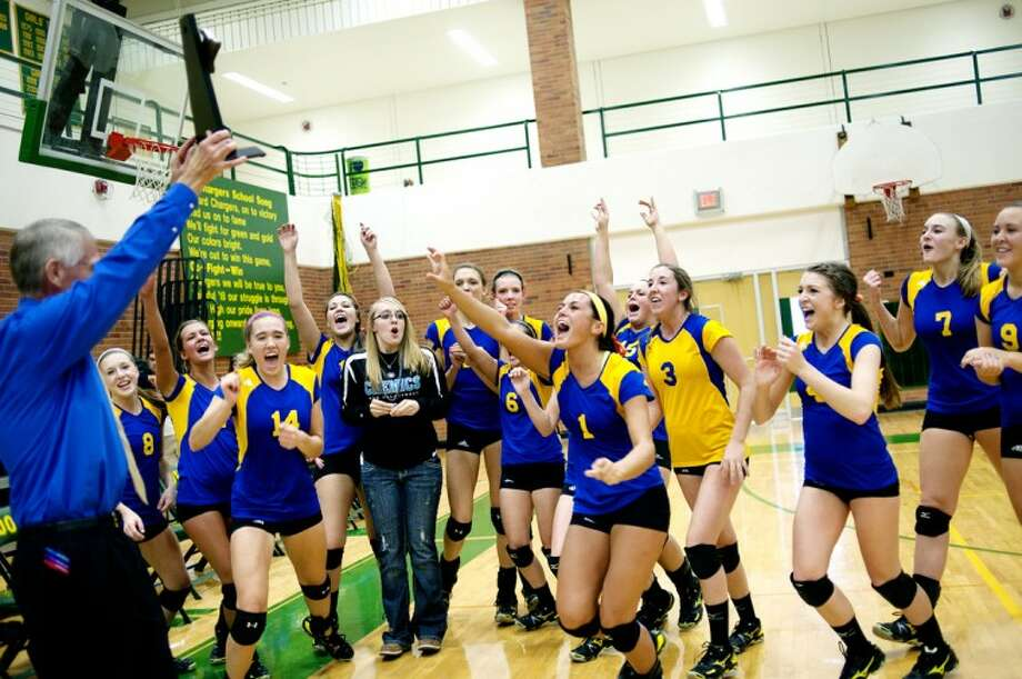 NICK KING | nking@mdn.net The Midland Chemics celebrate their district championship as coach Tim Zerull, left, holds up the trophy Saturday after beating Dow at Dow High School. Photo: Nick King/Midland  Daily News