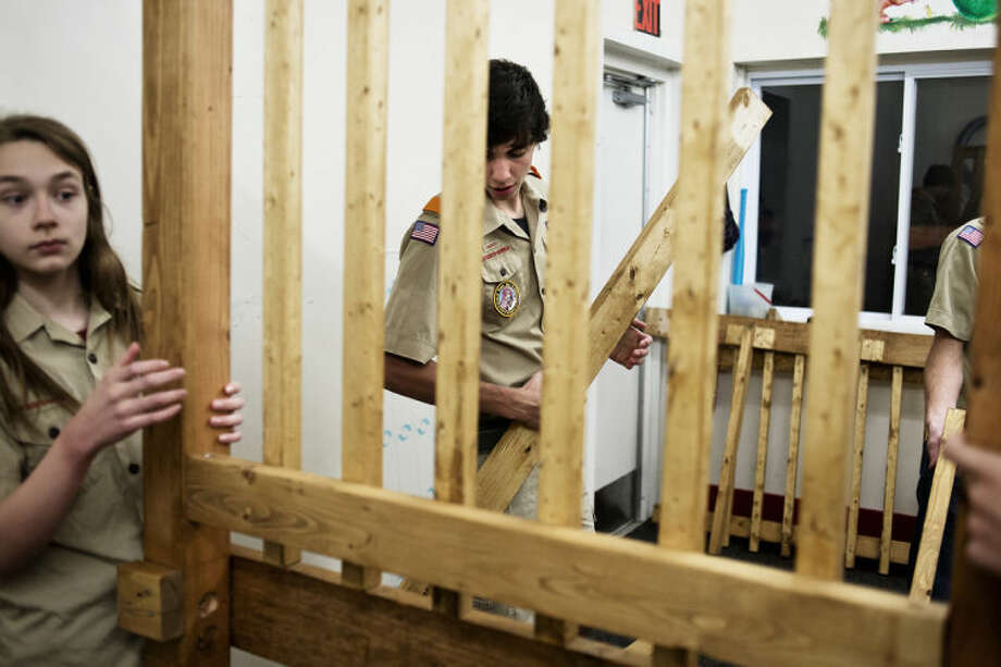 "NEIL BLAKE | nblake@mdn.netAndrew Thornton, 14, center, works on his Eagle Scout project as Gabriel Swartzmiller, 14, left, assists at the Chippewa Cooperative Preschool. Thornton was a student at the school 10 years ago and decided to construct a play structure there for his project. ""When he decided to do this for us, we were just thrilled,"" Debbie Carpenter, a teacher at the school, said. Photo: Neil Blake/Midland  Daily News"