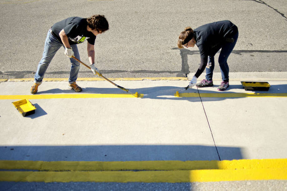 NICK KING | nking@mdn.netChemical Bank employees Leslie Toland, left, and Ann Beck paint lines outside of Plymouth Elementary School on Monday as part of Chemical Bank Care Day Initiative. All Michigan Chemical Bank locations were closed on Monday and employees participated in community service projects. Photo: Nick King/Midland  Daily News