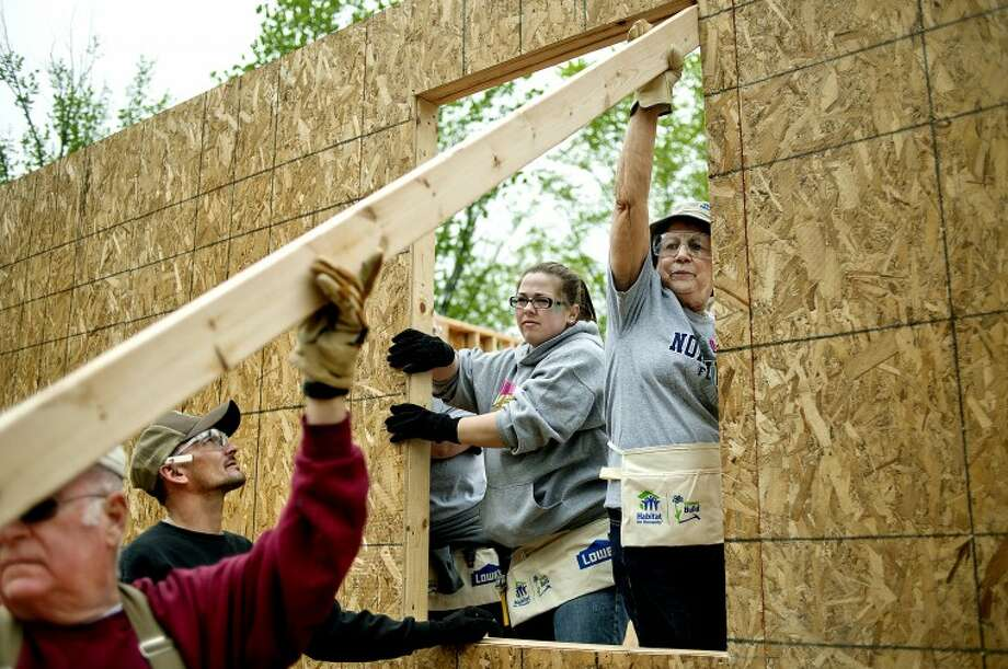 NICK KING | nking@mdn.net From left, volunteer Pat Fagan, property owner Tyler Nicholson, and Northwood employee volunteers Alexis Buchoz and Linda Dick work on a wall at a home being built off North Gordonville Road in Midland County. Photo: Nick King/Midland  Daily News