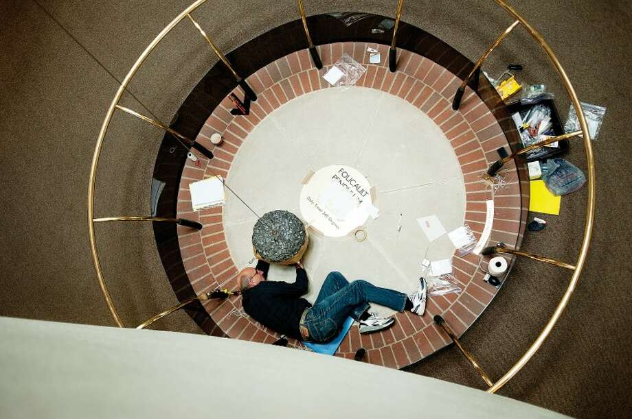 NEIL BLAKE | nblake@mdn.net Michigan State Professor David Smitley conducts measurements on the Foucault Pendulum at the Midland Center for the Arts on Tuesday, April 24. Smitley, an entomologist, started studying the Coriolis effect a few years ago as a side project and is gathering data for an upcoming research paper. Photo: Neil Blake/Midland  Daily News