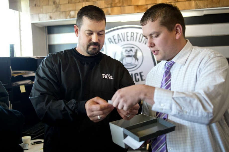 NICK KING | nking@mdn.net Beaverton City Police Sgt. Jason Campbell, right, and Gladwin County Board Chair Josh Reid pick a name out of a box during a prize give away Thursday during an open house at the Beaverton City Police Department. Area businesses donated gift certificates and items to be given away as door prizes. Various local employees and elected officials were on hand to answer questions about the upcoming millage and the local city and mayoral races. Food was served for guests as well. Photo: Nick King/Midland  Daily News