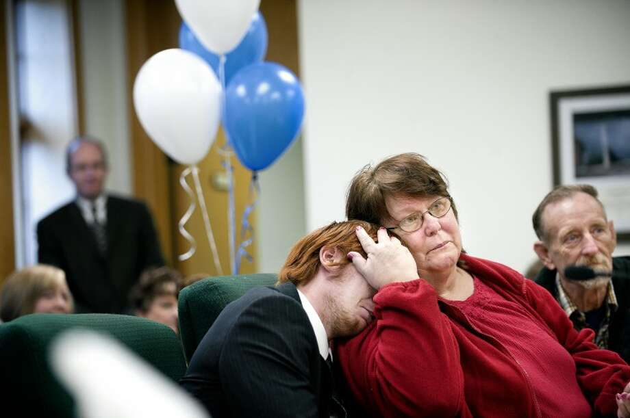 Sunny Lalone, right, hugs her newly adopted son Matthew, 17, during an adoption finalization hearing in Midland County Probate Court Judge Dorene Allen's courtroom Tuesday. Tuesday was Michigan Adoption Day and four children were officially adopted in Judge Allen's courtroom. Photo: NICK KING | Nking@mdn.net