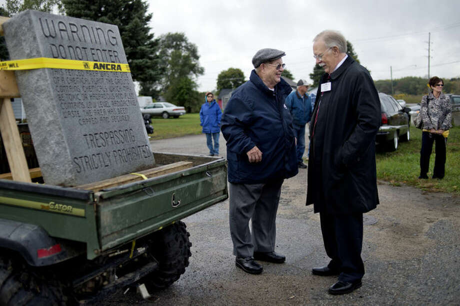 NICK KING | nking@mdn.netCity Councilman Bill Shrum, left, and Mayor Jim Kelly talk near the tombstone outside the old chemical plant site in St. Louis on Wednesday before the start of the parade to move the tombstone to its new location at the St. Louis Area Historical Society. Photo: Nick King/Midland  Daily News