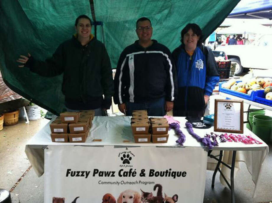 Photo provided From left: Candice Weeks, Chuck Moore and Melanie Hafelein of Fuzzy Pawz Outreach selling dog treats at the Midland Farmer's Market.