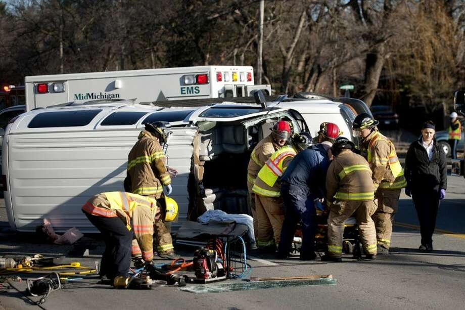 NICK KING | nking@mdn.netMidland Fire Department firefighters and EMS staff move the driver of a passenger van that rolled over during a two-vehicle accident onto a stretcher after working to extricate the woman this morning on southbound Eastman Avenue between Sylvan Lane and Pheasant Ridge Drive. The driver of the van suffered injuries and was transported from the scene by ambulance. The driver of a second vehicle was treated for minor injuries on scene and released. Southbound lane of Eastman Avenue was closed for more than an hour. Police detoured southbound traffic at Dilloway Drive and northbound traffic on Eastman Avenue was limited to one lane while rescue workers tended to the injured and cleaned up. The cause of the accident is under investigation. Photo: Nick King\u002fMidland  Daily News