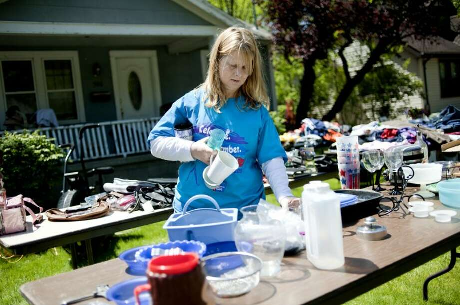 NICK KING | nking@mdn.net Julie Creasman arranges items on a table during her Relay For Life team garage sale Thursday on Ashman Street. Juile, along with her husband Dale and 15-20 other team members have a garage sale each year to raise funds for the organization. Photo: Nick King/Midland  Daily News