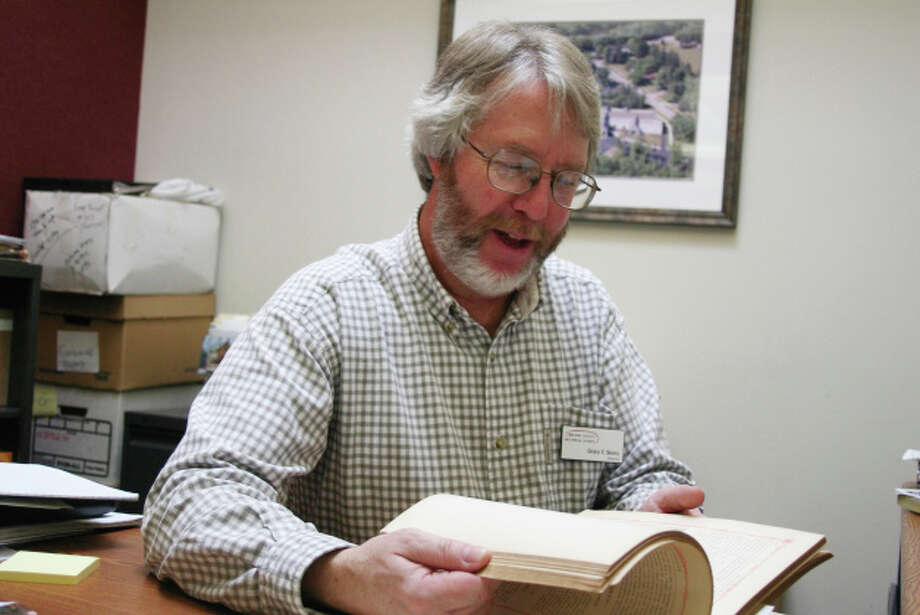 """Gary Skory, director of the Midland County Historical Society, reads from the book, """"Portrait and Biographical Album, Midland County, Mich.,"""" which was published in 1884. Photo: Lisa Satayut 