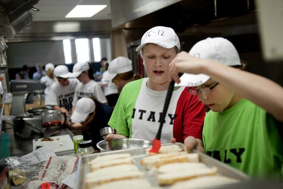 NICK KING | nking@mdn.netTeam Italy members Damian Turowski, right, and Vincent Van Pelt work on the toasted bread that the group was serving with their dish during the Iron Chef competition at St. Brigid as part of the Food Club 101. Photo: Nick King/Midland  Daily News