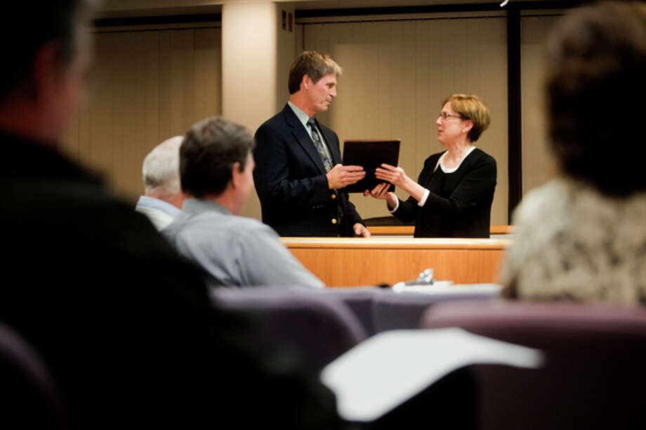 Mayor Maureen Donker presents retiring Assistant City Manager Jack Duso with a plaque and proclamation recognizing him for his years of service during the city council meeting last week. Photo: SEAN PROCTOR   For The Daily News
