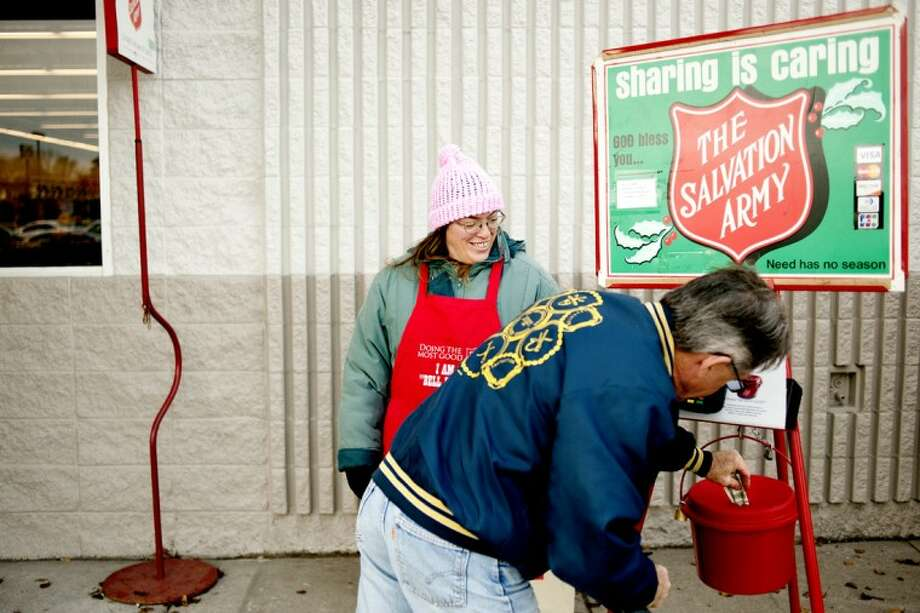 Susan Best, left, in her third year as a Salvation Army bell ringer, works outside Save-A-Lot in Midland as Tim Hazen of Midland drops in four dollars. The Midland Salvation Army had just kicked off its Red Kettle Campaign for this holiday season. Photo: THOMAS SIMONETTI | Tsimonetti@mdn.net