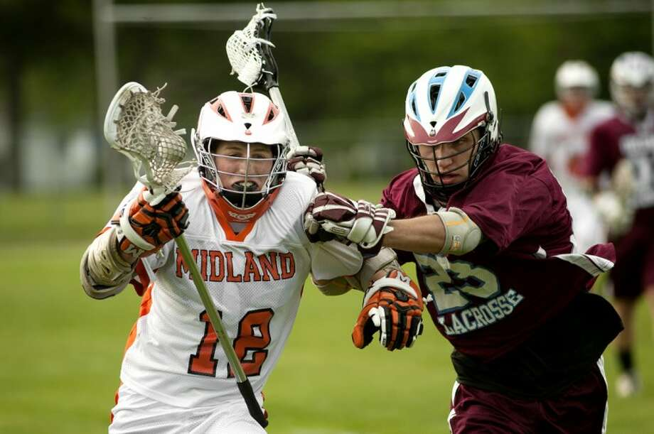NICK KING | nking@mdn.netMidland's Matthew Bausch, left, fights off Okemos' Maxwell Fagan during the first quarter Tuesday at Central Middle School. Photo: Nick King/Midland  Daily News