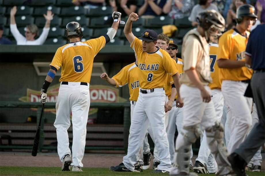 NICK KING | nking@mdn.netMidland High's Alex Rapanos, left, celebrates his run with Chase Toland in the sixth inning Monday at Dow Diamond.