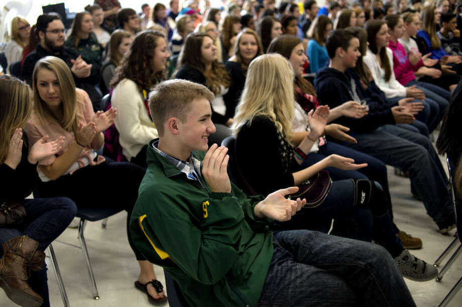 "NICK KING | nking@mdn.netDow High sophomore Justin Savage, center, claps along as the band Baladino plays a version of the Beatles' song ""Come Together"" during a performance for Midland and Dow High School students Tuesday in the Midland band room. Photo: Nick King/Midland  Daily News"