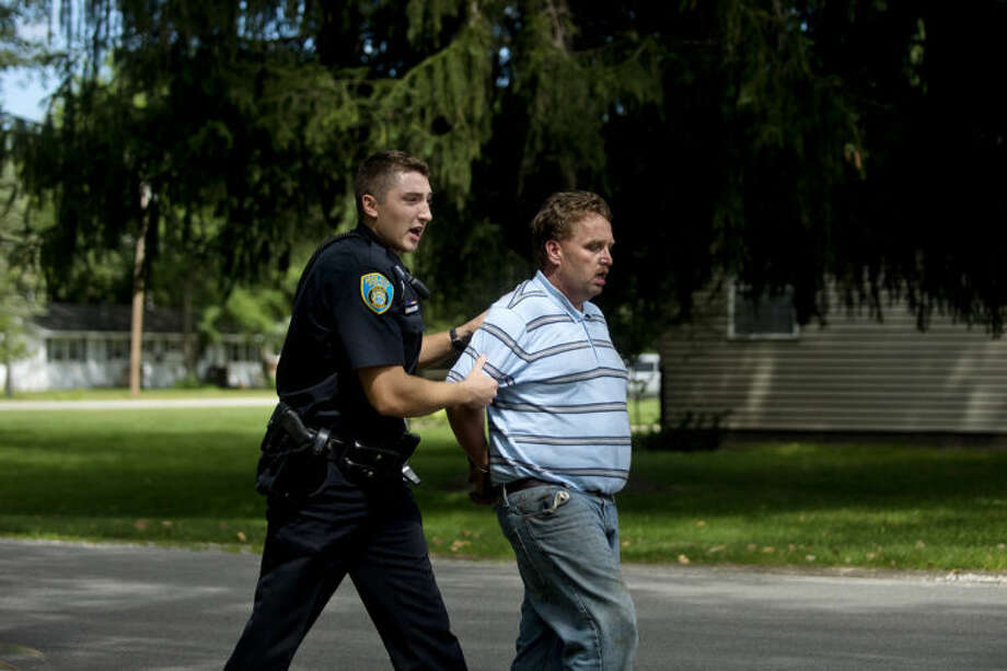 NICK KING | nking@mdn.netMidland Police Officer Travis Toth, left, walks a handcuffed Charles Scott Martin to a police cruiser after Martin ran from police at a home in Midland in August. Toth, his field training officer Paul McDonald and Officer Josh Thielen chased Martin through a corn field, caught and arrested him. Photo: Nick King/Midland  Daily News