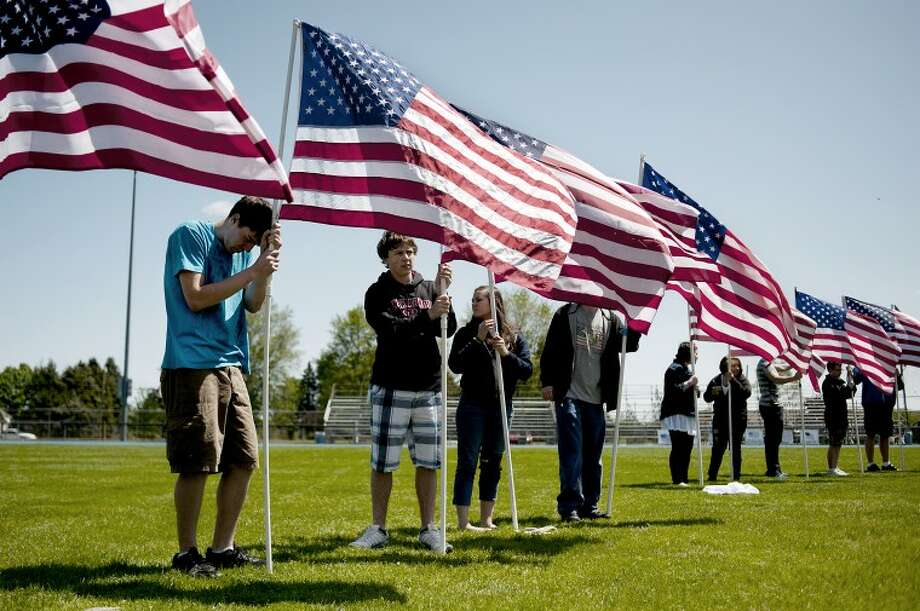 NEIL BLAKE | nblake@mdn.netHemlock High School students hold flags in a semi circle around the podium on the football field during a tribute to veterans at the high school. The tribute included the VFW Post 7302, veteran skydivers and the Michigan Patriot Guard riders. Photo: Neil Blake/Midland  Daily News