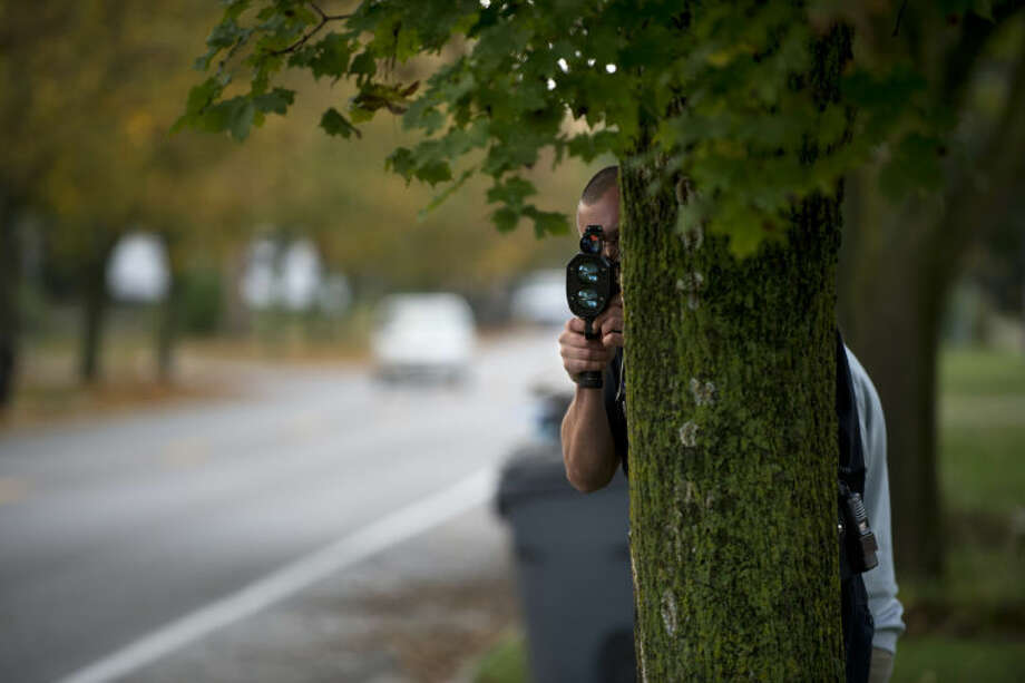 NEIL BLAKE | nblake@mdn.netMidland Police Officer Scott Coyle looks for speeders on Swede Avenue on Wednesday. Coyle clocked cars as they passed and then alerted police officers waiting down the street of violators. Photo: Neil Blake/Midland  Daily News