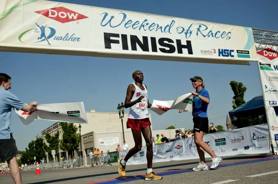 NICK KING | nking@mdn.netEdward Korir crosses the finish line Sunday during The Qualifier Marathon in downtown Bay City. Korir won the race. Photo: Nick King/Midland  Daily News
