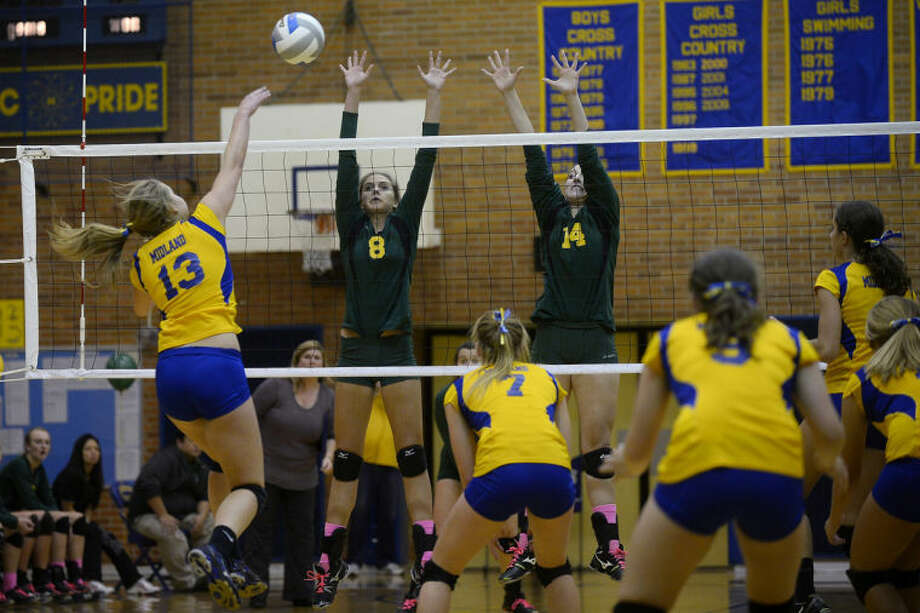 SEAN PROCTOR | sproctor@mdn.netMidland's Taylor Jensen hits the ball as Dow's Keely McCaffrey, center, and Jenna Queary look to block it Wednesday evening during their game at Midland High School.
