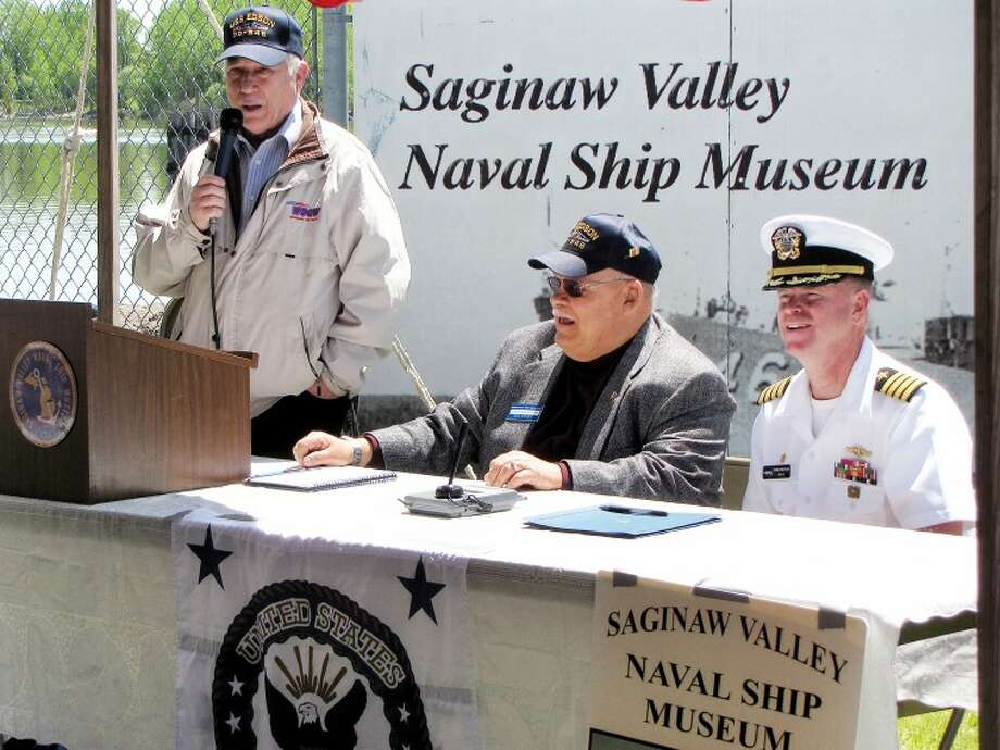 Erich T. Doerr | for the Daily NewsWSGW radio personality Art Lewis, far left, talks to the crowd before Saginaw Valley Naval Ship Museum President Mike Kegley, middle, and U.S. Navy Captain Chris Pietras signed official paperwork handing over ownership of the Navy's destroyer USS Edson to the museum for preservation in Bay City.