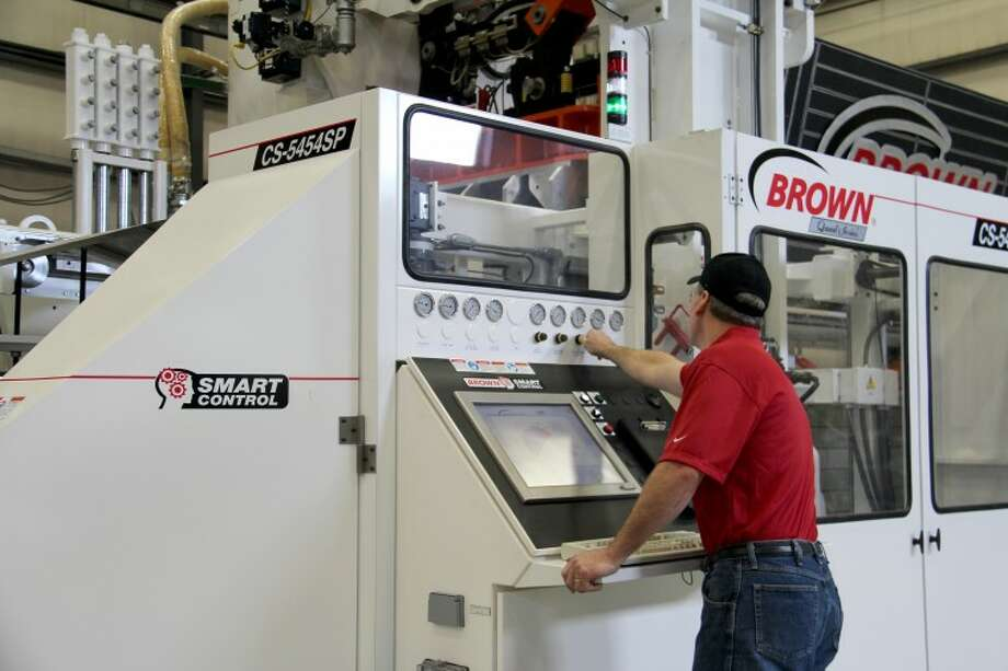 Photos ProvidedJim Martin, Brown Machine's vice president of thermoforming process engineering, makes a process adjustment on one of the company's machines.