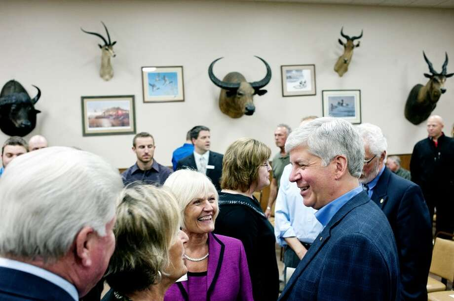 THOMAS SIMONETTI | tsimonetti@mdn.net Governor Rick Snyder, right, talks with supporters before an event hosted by the Mid Michigan Community College Foundation at Jay's Sporting Goods in Clare on Friday. Photo: Thomas Simonetti