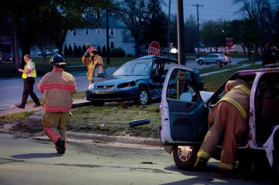 NEIL BLAKE | nblake@mdn.netMidland City Fire Department firefighters work to clear the scene of a two-car accident at the intersection of Carpenter Street and Patrick Road on Monday evening. The crash kept the intersection closed for 2 1/2 hours. Photo: Neil Blake/Midland  Daily News