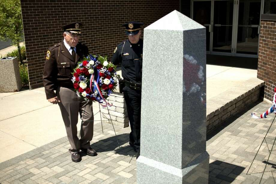 NEIL BLAKE | nblake@mdn.netMidland County Sheriff Jerry Nielsen, left, and Midland Police Chief Clifford Block lay a wreath at the base of the police memorial at the Law Enforcement Center in Midland on Tuesday. This week is National Police Week, which is designed to recognize the service and sacrifice of U.S. law enforcement officials. To date, 37 officers have been killed in the line-of-duty nationally in 2012.