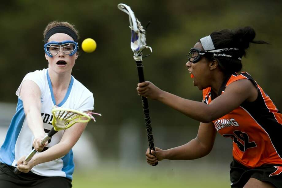 JAKE MAY | for the Daily NewsMidland's Anna Lunsford takes a shot while Flushing's Adrianne Bright attacks on defense Tuesday afternoon at Northeast Middle School. Midland beat Flushing 15-6.