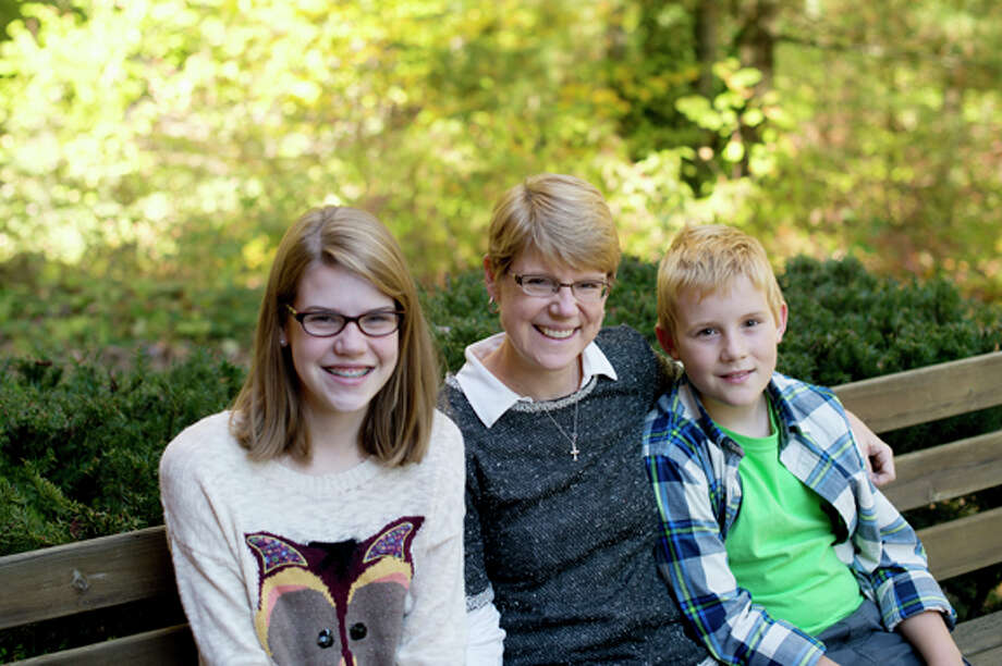"Ansley Dauenhauer, center, is pictured with her children, Maddie, 12, and Joseph, 10, at her home. Dauenhauer was diagnosed with breast cancer in 2007 and looked for a book to read to Maddie to help her process the diagnosis and that told the story of someone going through cancer for an older elementary student. Finding none, she decided to write one herself. ""Cancer Slam"" was published last year. Photo: Neil Blake/Midland  Daily News / Midland Daily News"