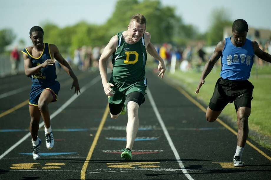 NEIL BLAKE | nblake@mdn.netDow's Brent Acton, center, crosses the line during the 100 meter dash at the regional track meet at Bay City Western on Friday. Photo: Neil Blake/Midland  Daily News