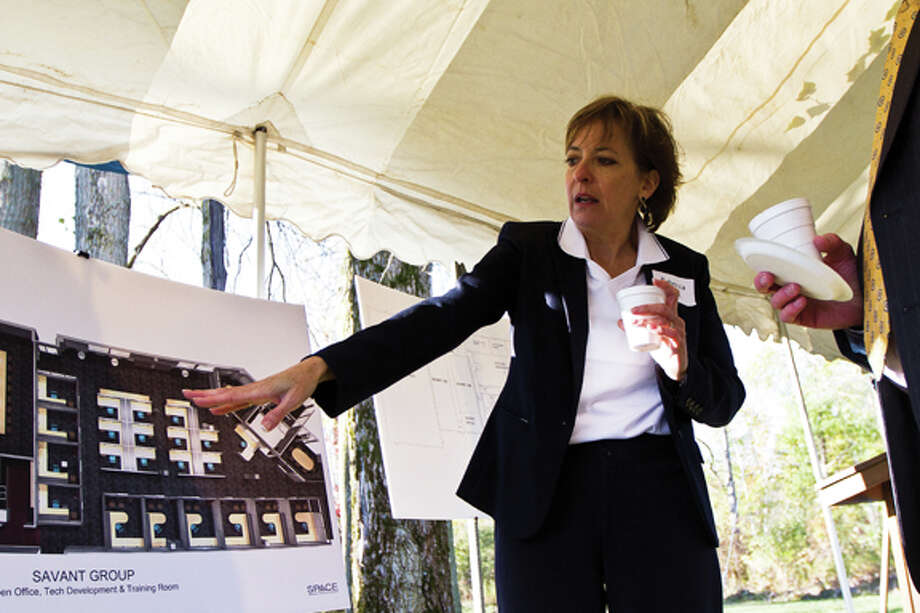 CHUCK MILLER | for the Daily News Rebecca Cox, president of Savant Group,  shows the blueprints for the 11,000-square-foot expansion, which will house a technical training facility. The proposed finish date is late spring or early summer. / Midland Daily News