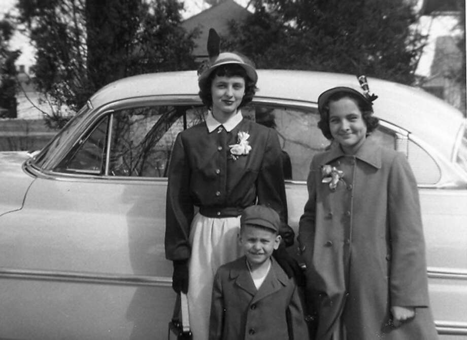 "This is Nancy (LePard) Barker at the age of 13 proudly wearing an Easter outfit that she made after learning about ""sewing"" from a Girl Scout leader. Nancy is wearing a tan linen sheath dress with a dark brown Eisenhower jacket. Her younger sister, Peggy, is next to her and brother, Chuck, is in front of his sisters."