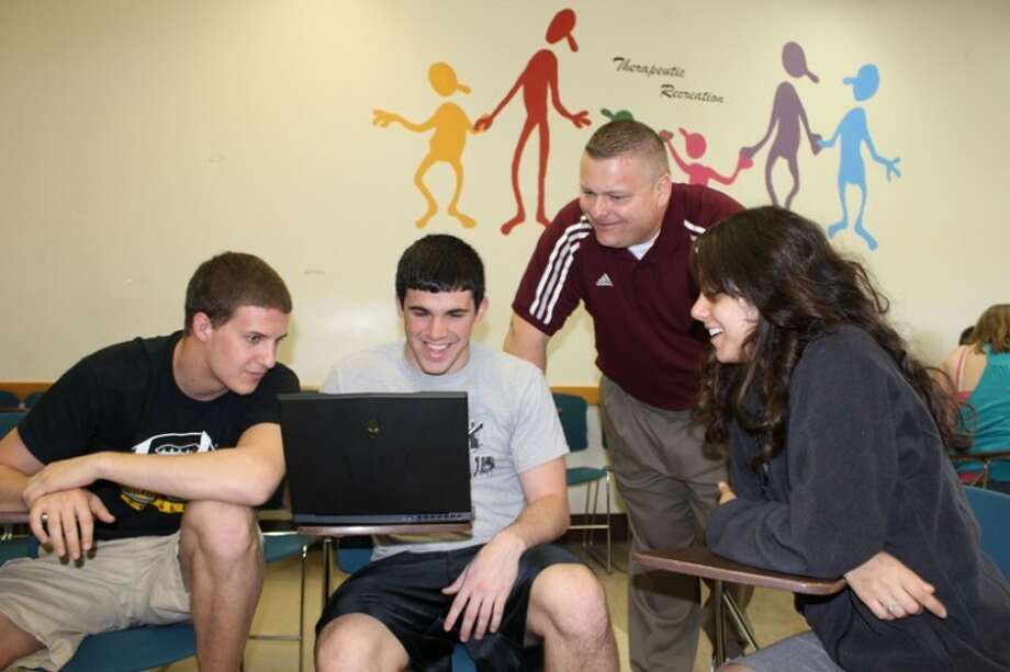 Submitted photoCentral Michigan University assistant professor Eric Buschlen shares a laugh with students while working on a leadership project at the close of the semester at CMU.